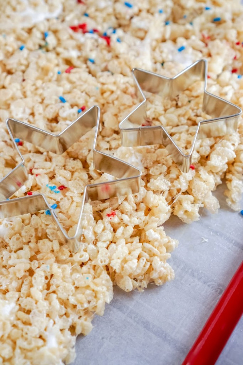 Red, White, and Blue Rice Krispie Treat Stars- Celebrate patriotic holidays in style with these delicious patriotic rice krispie treat stars! They are festive, fun, and a crowd-pleaser! | homemade krispy rice treat recipes, red, white, and blue food recipes, patriotic dessert recipes, #memorialDay #fourthOfJuly #riceKrispieTreats #dessertRecipe #ACultivatedNest